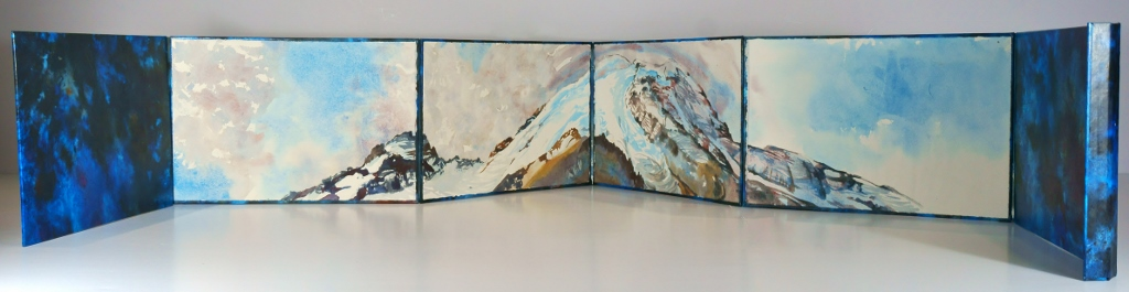 Photo of Suze Woolf accordion-fold artist book with watercolor painting of Mt. Rainier